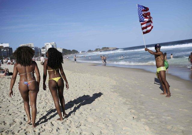 A man holds a U.S. flag as women walk on Ipanema beach in Rio de Janeiro, Brazil on August 13, 2016. (Photo by Nacho Doce/Reuters)