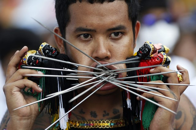 A devotee of the Ban Tha Rua Chinese shrine with his cheeks pierced with different spikes takes part in a street procession celebrating the annual vegetarian festival in Phuket September 28, 2014. (Photo by Damir Sagolj/Reuters)