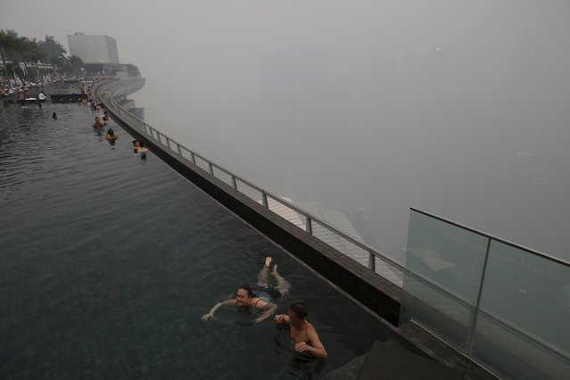 Tourists swim in an infinity pool overlooking the skyline of the central business district shrouded by haze in Singapore September 14, 2015. Indonesia said on Friday it will send more than 1,000 troops to fight fires in southern Sumatra, as smoke makes thousands sick, delays flights and pushes air quality to unhealthy levels in neighboring Singapore and Malaysia. (Photo by Edgar Su/Reuters)