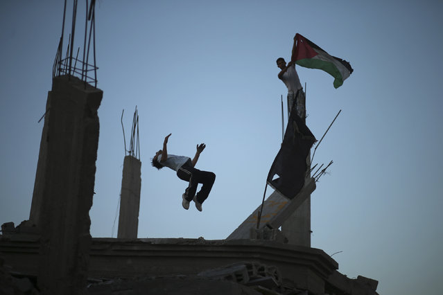 A Palestinian youth holds a Palestinian flag as his another practices Parkour skills over the ruins of house, which witnesses said was destroyed during a seven-week Israeli offensive, in the Shejaia neighborhood east of Gaza City October 1, 2014. (Photo by Mohammed Salem/Reuters)