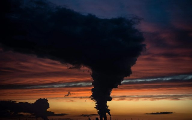 A red and blue colored sky is pictured at sunset as steam rises from the chimneys of Niederaussen lignite-fired power plant in Roggendorf, western Germany on November 8, 2019. (Photo by Federico Gambarini/dpa/AFP Photo)