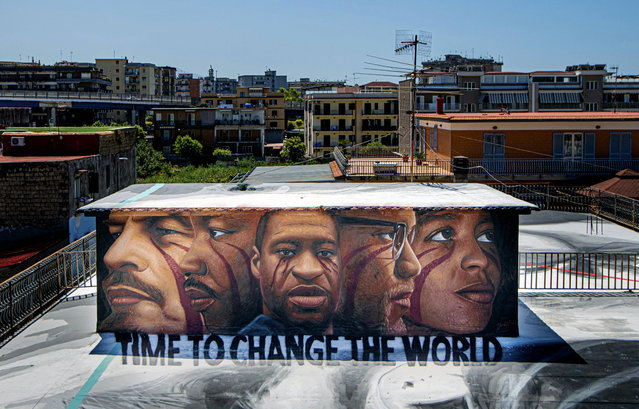 A mural by street artist Jorit, honoring George Floyd, who died May 25 after being restrained by police in Minneapolis, USA, depicts from left, Lenin, Martin Luther King, George Floyd, Malcom X and Angela Davis, atop the roof of a building in Naples, southern Italy, Saturday, June 6, 2020. (Photo by Alessandro Pone/LaPresse via AP Photo)
