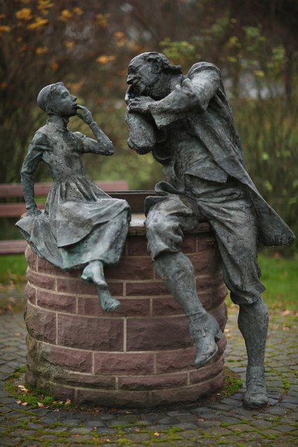 """A bronze sculpture depicts a grandfather recounting a fairy tale to his dranddaughter on November 19, 2012 in Schoeneberg, Germany. Schoeneberg lies along the """"Fairy Tale Road"""" (in German: Die Maerchenstrasse) that leads through the region between Frankfurt and Bremen where the Grimm brothers collected and adapted most of their fairy tales, which include such global classics as Sleeping Beauty, Little Red Riding Hood, Rapunzel, Cinderella and Hansel and Gretel, in the early 19th century. The 200th anniversary of the first publication of the stories will take place this coming December 20th.  (Photo by Sean Gallup)"""