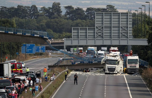 The scene on the London-bound M20 motorway, about 30 miles (48 kilometers) southeast of the capital, after a lorry hit a pedestrian bridge, causing it to collapse, Saturday August 27, 2016. Witnesses and emergency services say a truck has struck an overpass and collapsed a pedestrian bridge onto one of England's busiest motorways, the M20, injuring one person. (Photo by Steve Parsons/PA Wire via AP Photo)
