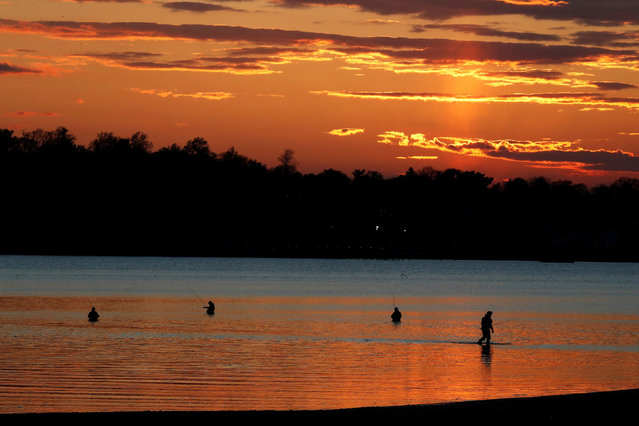 People are seen in silhouette fishing in Manhasset Bay as the coronavirus disease (COVID-19) continues to spread, in Port Washington, New York, U.S., April 28, 2020. (Photo by Shannon Stapleton/Reuters)