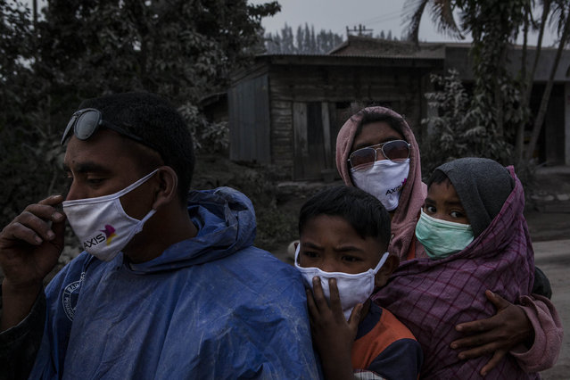 A family cover their face as passing through an area covered by ash after Mount Sinabung erupted spewing volcanic materials on October 13, 2014 in Berastagi, Karo district, North Sumatra, Indonesia. Mount Sinabung, which had lain dormant for over 400 years, has been intermittently erupting since September 15 last year, killing 15 people and forcing hundreds to flee their homes. According to The National Disaster Mitigation Agency, more than 3,000 residents are still displaced. (Photo by Ulet Ifansasti/Getty Images)