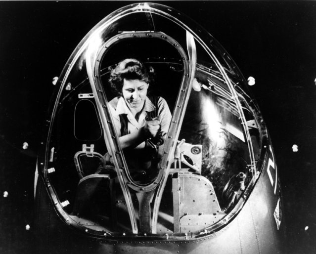"""A female technician fits the bombsight mount of a B-17F heavy bomber nearing completion in Long Beach, Calif. on September 23, 1943, during World War II. The mount will carry the world's deadliest bombsight. Better known as the """"Flying Fortress"""", the B-17F is a later model of the B-17. (Photo by AP Photo)"""
