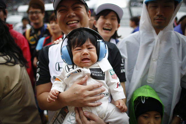 A seven-month-old boy wearing earmuffs cries as his father lifts him up during a pitlane walk for fans outside the Mercedes garage at the Suzuka Circuit in Suzuka, central Japan, 24 September 2015. The Japanese Formula One Grand Prix will be held on 27 September 2015. (Photo by Diego Azubel/EPA)