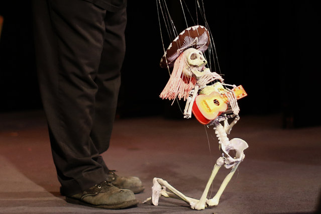 A puppeteer controls a marionette during a performance at the Bob Baker Marionette Theater in Los Angeles, California October 17, 2014. (Photo by Lucy Nicholson/Reuters)