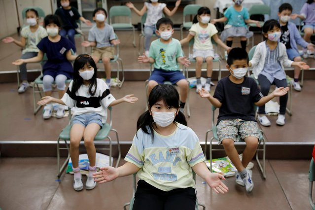 Students wearing protective face masks amid the coronavirus disease (COVID-19) outbreak, clap along instead of singing a song during a music class at Takanedai Daisan elementary school, which practices various methods of social distancing in order to prevent the infection, in Funabashi, east of Tokyo, Japan on July 16, 2020. (Photo by Kim Kyung-Hoon/Reuters)