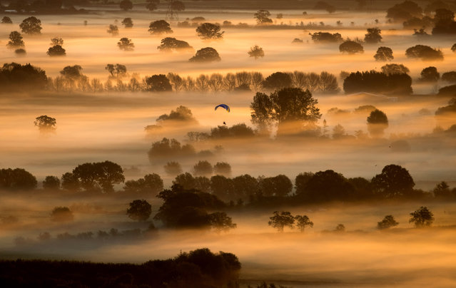 Early morning mist lingers in fields as the autumn sun rises over the Somerset Levels as viewed from Glastonbury Tor near Glastonbury on September 22, 2017 in Somerset, England. Today marks the start of the astronomical autumn, which is defined by the Earth's axis and orbit around the sun. The transition from summer to autumn is defined by the autumn equinox, when day and night are of roughly equal length, but also signals that the nights will become increasingly longer than the days until the spring equinox, when the pattern is reversed. (Photo by Matt Cardy/Getty Images)