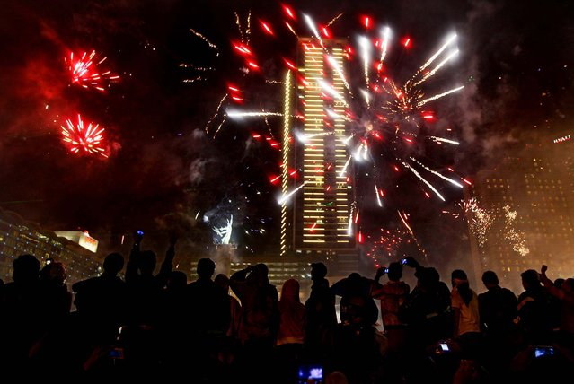 People watch fireworks in Jakarta, Indonesia. (Photo by Dita Alangkara/Associated Press)