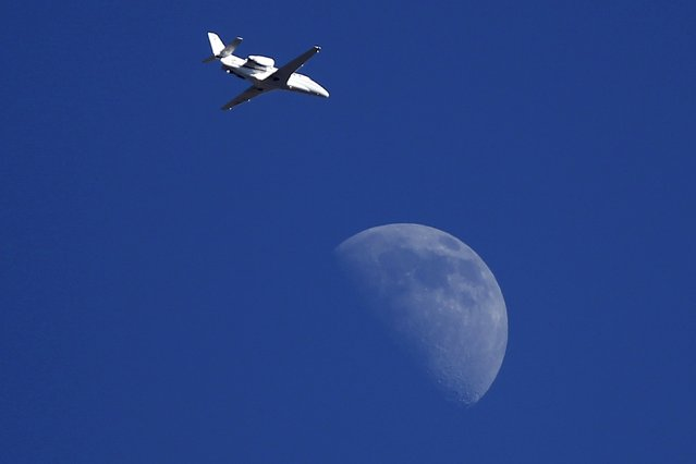 A jet flies past the moon over Ardales, near Malaga, southern Spain, August 23, 2015. (Photo by Jon Nazca/Reuters)