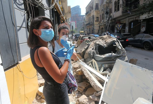 Young Lebanese women wearing protective masks and gloves against the coronavirus pandemic, stand on August 5, 2020 amid the rubble in Beirut's Gimmayzeh commercial district which was heavily damaged by the previous day's powerful explosion that tore through Lebanon's capital, resulting from the ignition of a huge depot of ammonium nitrate at the city's main port. Rescuers searched for survivors in Beirut after a cataclysmic explosion at the port sowed devastation across entire neighbourhoods, killing more than 100 people, wounding thousands and plunging Lebanon deeper into crisis. The blast, which appeared to have been caused by a fire igniting 2,750 tonnes of ammonium nitrate left unsecured in a warehouse, was felt as far away as Cyprus, some 150 miles (240 kilometres) to the northwest. (Photo by AFP Photo/Stringer)