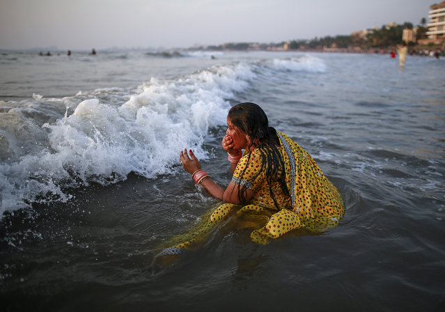 A Hindu devotee takes a dip in the waters of the Arabian Sea as she worships the Sun god Surya during the Hindu religious festival Chatt Puja in Mumbai October 29, 2014. (Photo by Danish Siddiqui/Reuters)