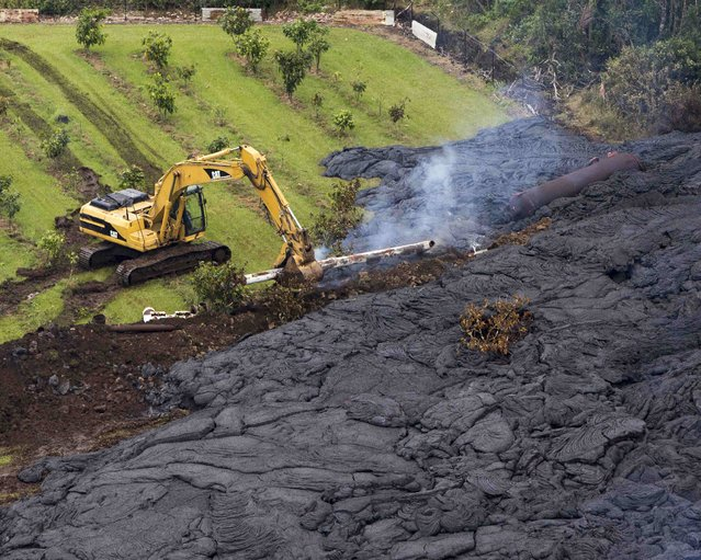 A construction crew tries to contain the lava flow from Mount Kilauea in Pahoa, Hawaii October 29, 2014. (Photo by Marco Garcia/Reuters)