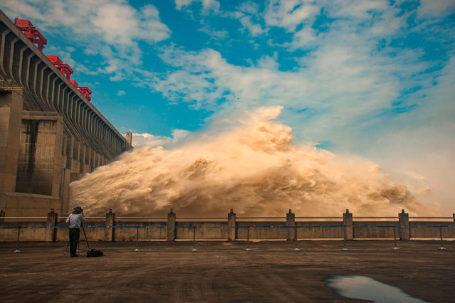 This photo taken on July 19, 2020 shows a person taking photos while water is released from the Three Gorges Dam, a gigantic hydropower project on the Yangtze river, to relieve flood pressure in Yichang, central China's Hubei province. Rising waters across central and eastern China have left over 140 people dead or missing, and floods have affected almost 24 million since the start of July, according to the ministry of emergency management. (Photo by AFP Photo/China Stringer Network)