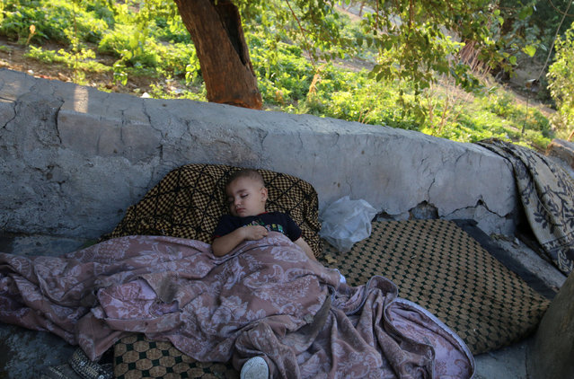 A boy sleeps outdoors in the rebel-held al-Sheikh Said neighbourhood of Aleppo, Syria September 1, 2016. (Photo by Abdalrhman Ismail/Reuters)
