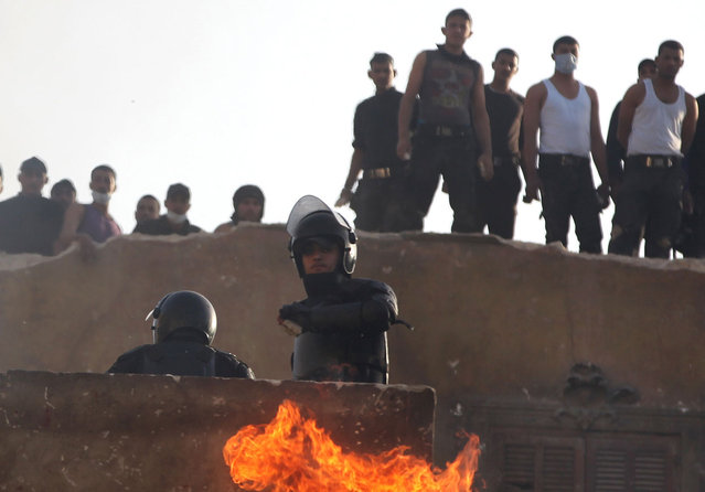A riot policeman watches as a thrown firebomb explodes on the wall below him, on a building overlooking demonstrators, near Tahrir Square, Cairo, Egypt, on January 26, 2013. (Photo by Khalil Hamra/AP Photo/The Atlantic)