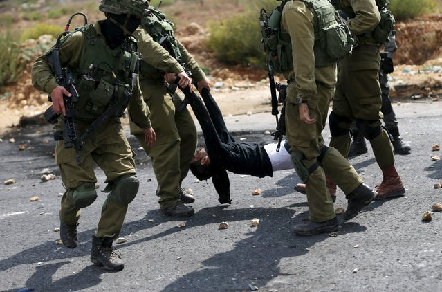 Israeli soldiers detain a wounded Palestinian protester during clashes near the Jewish settlement of Bet El, near the West Bank city of Ramallah, October 7, 2015. (Photo by Mohamad Torokman/Reuters)