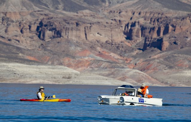 A kayaker looks over a 1965 Amphicar, driven by Dean Baker of Lake Havasu, Arizona, during the first Las Vegas Amphicar Swim-in at Lake Mead near Las Vegas, Nevada October 9, 2015. (Photo by Steve Marcus/Reuters)