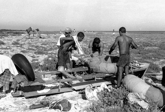 People prepare to launch a makeshift boat into the Straits of Florida towards the U.S., on the last day of the 1994 Cuban raft exodus in Havana, September 13, 1994. (Photo by Rolando Pujol Rodriguez/Reuters)