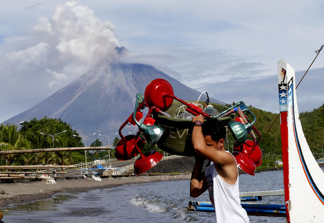 A fisherman unloads fishing equipment amidst a mild eruption of Mayon volcano Thursday, January 25, 2018 as seen from a village in Legazpi city, Albay province, around 340 kilometers (200 miles) southeast of Manila, Philippines. (Photo by Bullit Marquez/AP Photo)