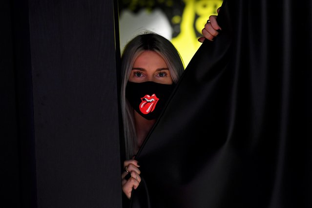 "A shop assistant wearing a face mask poses at the new flagship Rolling Stones store named ""RS No. 9 Carnaby"" in London, Britain, September 8, 2020. (Photo by Dylan Martinez/Reuters)"
