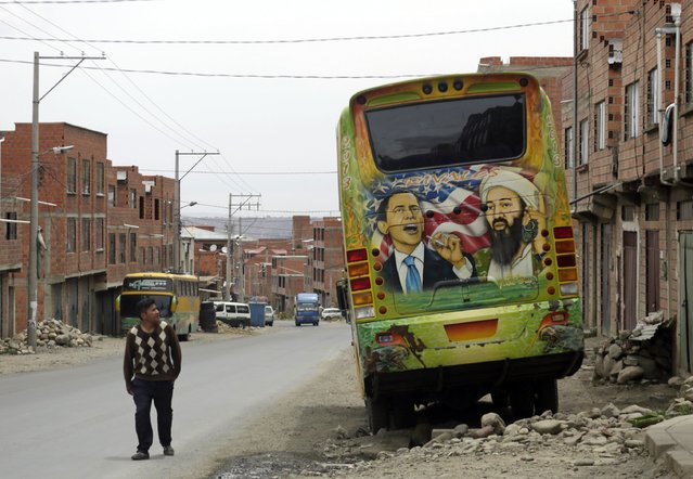 "A man looks at graffiti depicting U.S. President Barack Obama and Osama Bin Laden painted on the back of a bus in the outskirts of La Paz November 13, 2014. The word on the bus reads, ""Rivals"". (Photo by David Mercado/Reuters)"