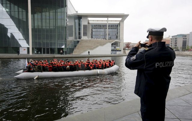 A policeman takes a picture of an original dinghy, used by migrants, carrying members of the parliament and volunteers on the river Spree to show conditions under which migrants cross the Mediterranean Sea, during an event organized by German NGO Sea-Watch near the Reichstag building in Berlin, Germany, October 13, 2015. (Photo by Fabrizio Bensch/Reuters)