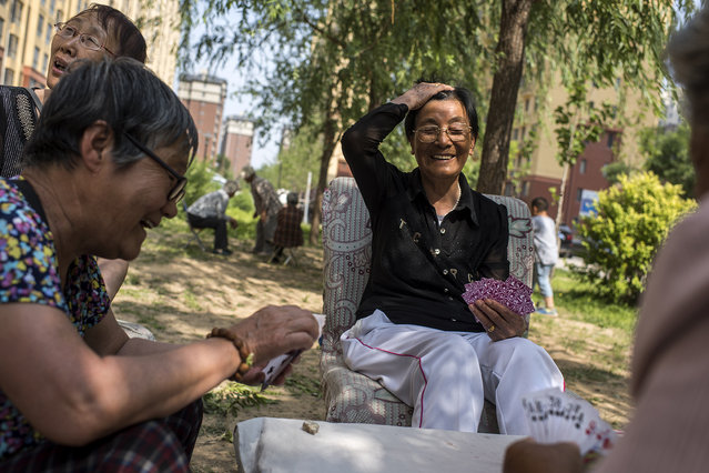 Zhang Shuying, center, plays cards with her friends and neighbors in Yanjiao, a rapidly expanding satellite city of over 700,000 people, outside Beijing, on May 21, 2016. Shuying, 80, used to farm on the land where the high rise apartment blocks she lives in now stand. (Photo by Michael Robinson Chavez/The Washington Post)