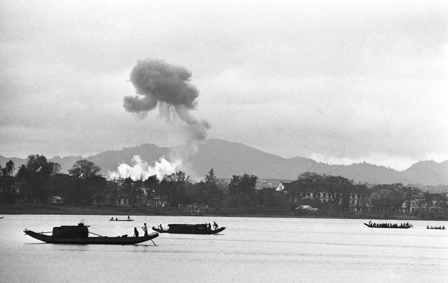 Napalm air strikes raise clouds of smoke into gray monsoon skies as houseboats glide down the Perfume River toward Hue in Vietnam, on February 28, 1963, where the battle for control of the old Imperial City has ended with a Communist defeat. Firebombs were directed against a village on the outskirts of Hue. (Photo by AP Photo)