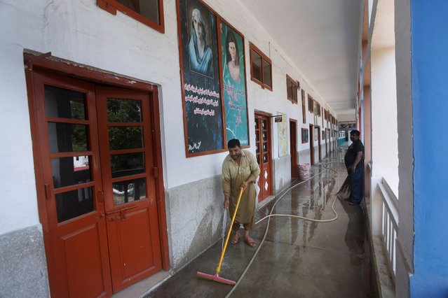 Workers wash a corridor of a school building in preparation for reopening schools that were closed in March, in Lahore, Pakistan, Thursday, September 10, 2020. Education officials in Pakistan say authorities will start reopening schools from Sept. 15 amid a steady decline in coronavirus deaths and infections. (Photo by K.M. Chaudary/AP Photo)