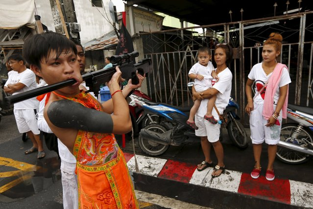 People look as a devotee of the Chinese Bang Neow shrine with a rifle pierced in his cheek, walks during a procession celebrating the annual vegetarian festival in Phuket, Thailand October 18, 2015. (Photo by Jorge Silva/Reuters)