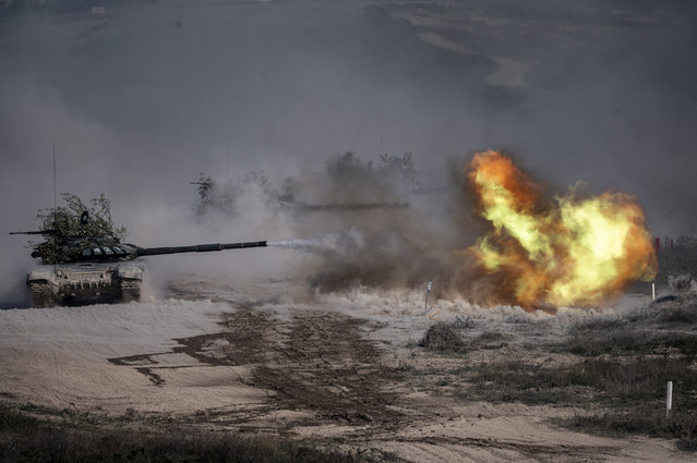"A Russian army T-72-B3 tank fires during military exercises at the Raevsky range in Southern Russia on September 23, 2020 during the ""Caucasus-2020"" military drills gathering China, Iran, Pakistan and Myanmar troops, along with ex-Soviet Armenia, Azerbaijan and Belarus. Up to 250 tanks and around 450 infantry combat vehicles and armoured personnel carriers will take part in the September 21 to 26 land and naval exercises that will involve 80,000 people including support staff. (Photo by Dimitar Dilkoff/AFP Photo)"
