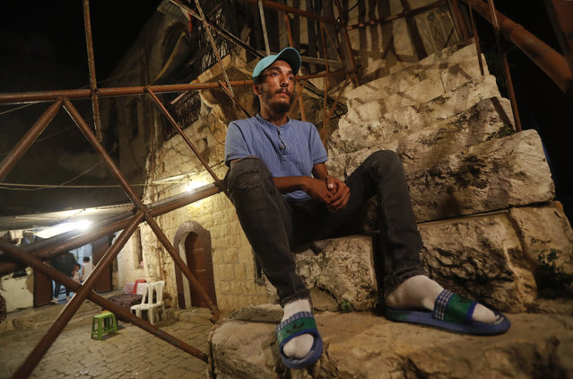 Lebanese Mohammed Sufian, 21, sits outside his house, in Tripoli, north Lebanon Thursday, September 17, 2020, days after he was rescued at sea by a U.N. naval force after trying to migrate with his family on a boat to Cyprus. He ended up losing his two-year-old son as a result of severe heat with no food or water on board. Mohammed is among dozens of people who have tried in recent weeks to flee Lebanon to Europe amid a devastating and unprecedented economic and financial crisis. (Photo by Hussein Malla/AP Photo)