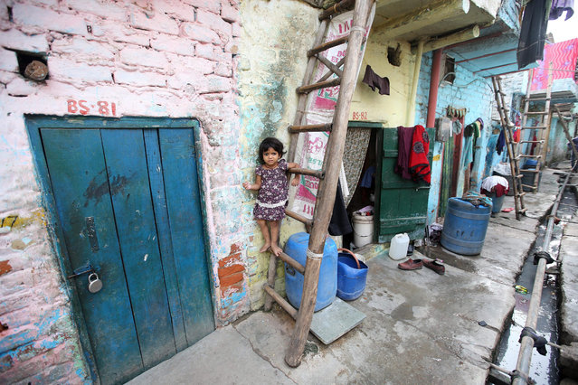 A young girl stands on a ladder in a slum area where a four-year-old girl was allegedly raped, New Delhi, India, 14 October 2015. According to media reports, two men are being questioned by police related to the rape of a 4-year-old girl in Delhi. The girl was found by some railway lines on 09 October and is in hospital with serious injuries. (Photo by Rajat Gupta/EPA)