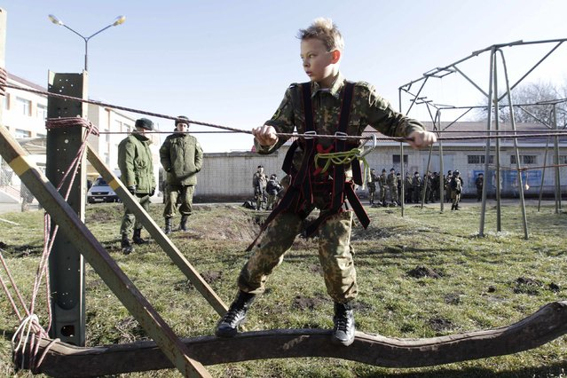 A student from the General Yermolov Cadet School crosses an obstacle during a competition between school classes in the southern Russian city of Stavropol, November 22, 2014. (Photo by Eduard Korniyenko/Reuters)