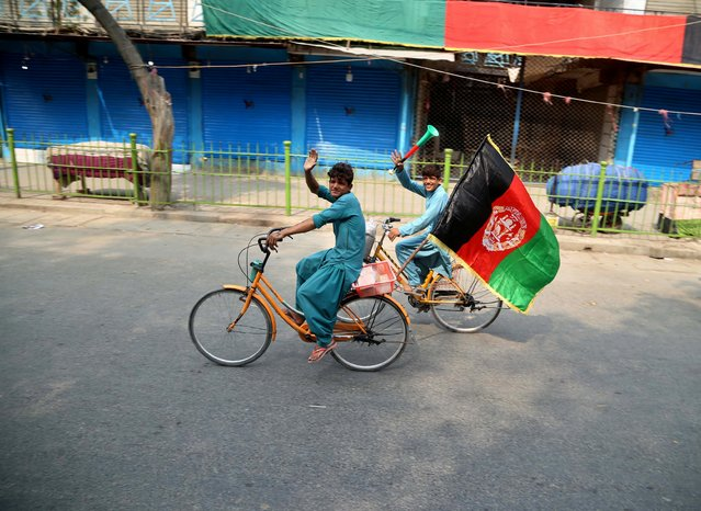 A boy waves Afghanistan's national flag as he rides his bicycle on Independence Day in Jalalabad, Afghanistan, 18 August 2020. Afghanistan i's celebrating the 101st anniversary of its independence from British rule on 18 August. (Photo by Ghulamullah Habibi/EPA/EFE)