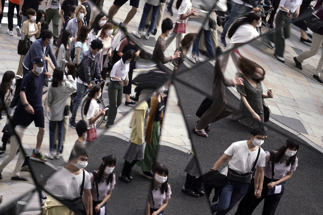 People wearing protective masks to help curb the spread of the coronavirus are reflected on mirror wall of a shopping building Monday, September 21, 2020, in Tokyo. The Japanese capital confirmed more than 90 coronavirus cases on Monday marking Respect-for-the-Aged Day holiday. (Photo by Eugene Hoshiko/AP Photo)