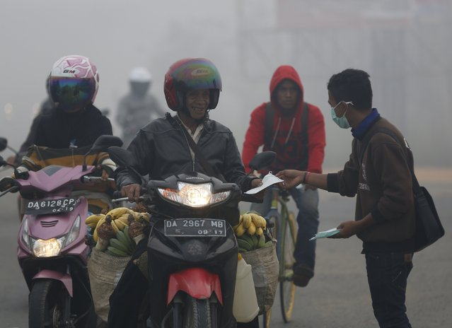 A student volunteer hands out protective masks to motorists near the south Kalimantan city of Banjarmasin October 28, 2015. Indonesia's weather agency failed to predict that the effects of the El Nino weather phenomenon this year would be worse than in 1997, a senior minister said on Wednesday, as the government considers declaring a national emergency due to forest fires. (Photo by Darren Whiteside/Reuters)
