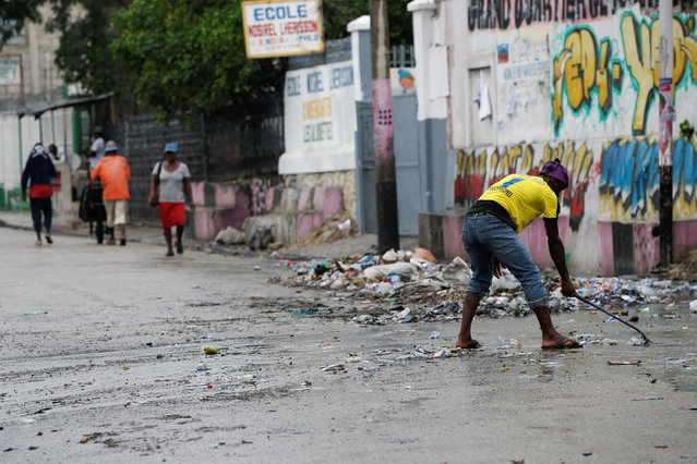A man tries to collects the garbage on a street while Hurricane Matthew approaches Port-au-Prince, Haiti, October 3, 2016. (Photo by Carlos Garcia Rawlins/Reuters)