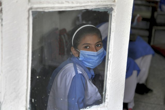 A student wearing a face mask to prevent the spread of the coronavirus looks out from her classroom at a primary school in Peshawar, Pakistan, Wednesday, September 30, 2020. Pakistani students head back to primary schools following their reopening, amid a steady decline in coronavirus deaths and infections. (Photo by Muhammad Sajjad/AP Photo)