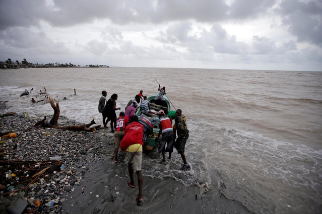 Residents push a boat into the sea after Hurricane Matthew in Les Cayes, Haiti, October 5, 2016. (Photo by Andres Martinez Casares/Reuters)