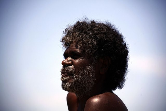 """Australian Aboriginal hunter Bruce Gaykamangu of the Yolngu people looks across a billabong at potential prey near the """"out station"""" of Ngangalala, located on the outksirts of the community of Ramingining in East Arnhem Land November 25, 2014. (Photo by David Gray/Reuters)"""