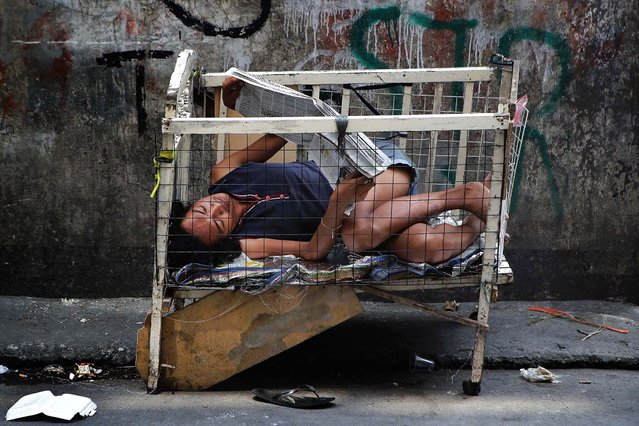 A man reads a newspaper inside a dilapidated baby's crib along a street in Manila, Philippines, on April 10, 2013. (Photo by Aaron Favila/Associated Press)