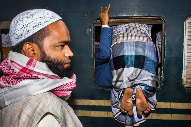 """Open travel and Bangladesh national award second-place winner: Md Enamul Kabir. """"It was the morning of 13 January 2017 at Kamalapur Railway Station, Dhaka, Bangladesh. Everybody was walking behind the train. Normally it's not so crowded, but that day it was. A passenger was trying to enter through the window because he could not go through the door"""". (Photo by Md Enamul Kabir/Sony World Photography Awards 2018)"""