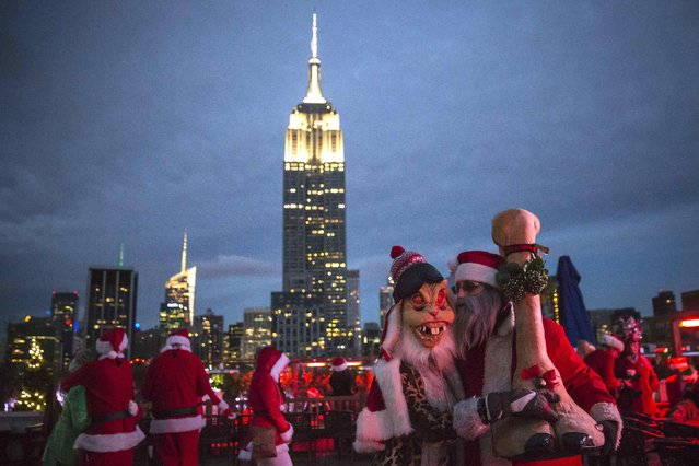 The Empire State Building is seen in the background as revelers taking part in SantaCon are pictured at a top a rooftop bar after sunset in Midtown Manhattan, New York  December 13, 2014. (Photo by Elizabeth Shafiroff/Reuters)