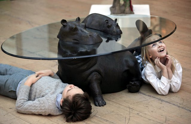 """Children lay underneath a hippoptamus' occasional table, as they pose for the photographers during a press preview of a themed auction that features the animal as artistic inspiration, entitled """"Creatures Great and Small"""", in London, Monday, December 15, 2014. (Photo by Lefteris Pitarakis/AP Photo)"""