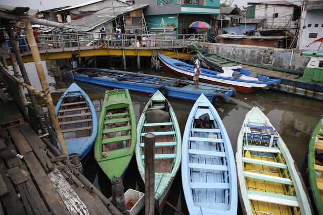 A boat passes under a bridge next to the seawall protecting Luar Batang, one of the oldest kampongs in Jakarta, dating back to the16th century, in north Jakarta in this October 7, 2014 file photo. (Photo by Darren Whiteside/Reuters)